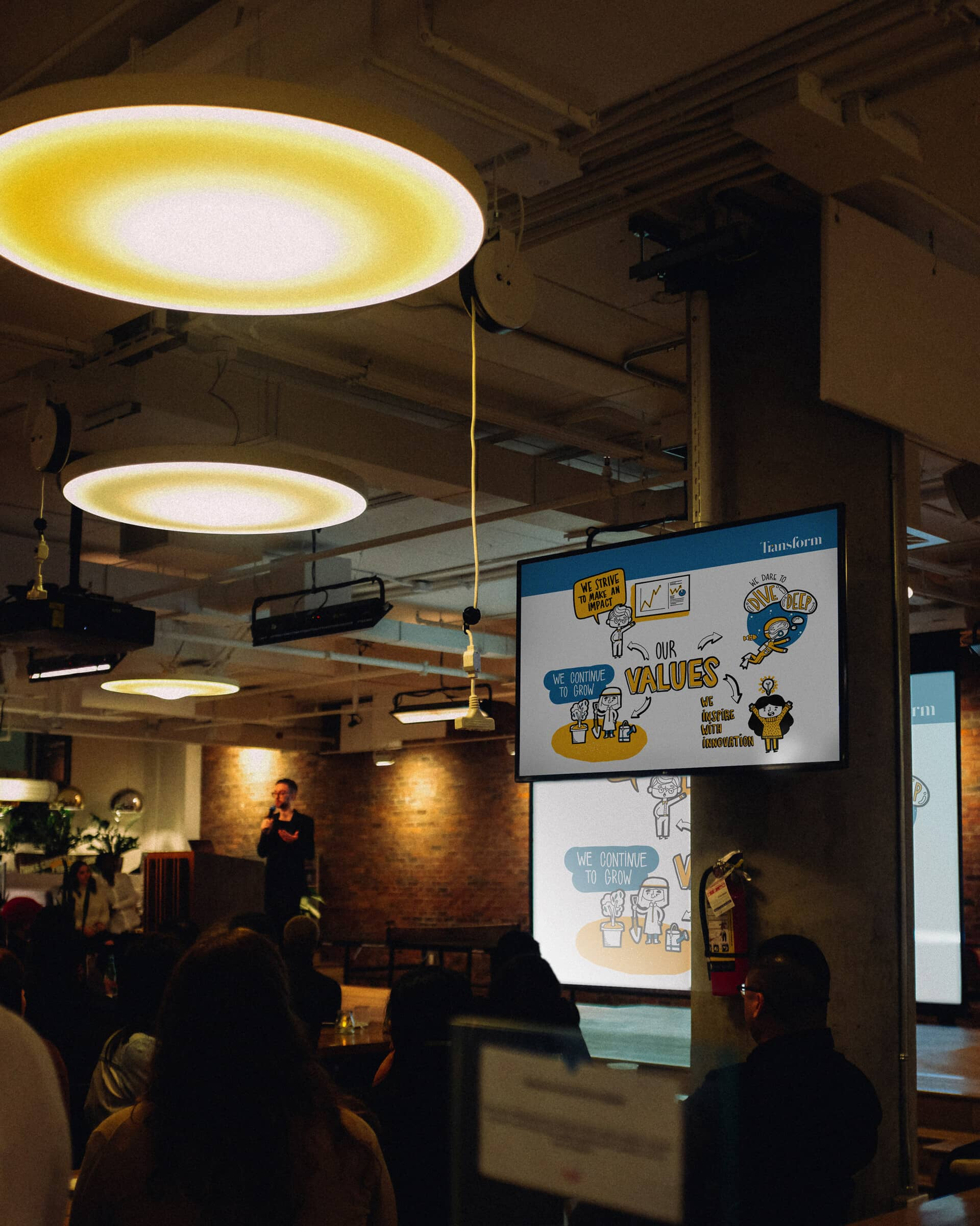 Transform's illustrated Values slide displayed on screens in a crowded room