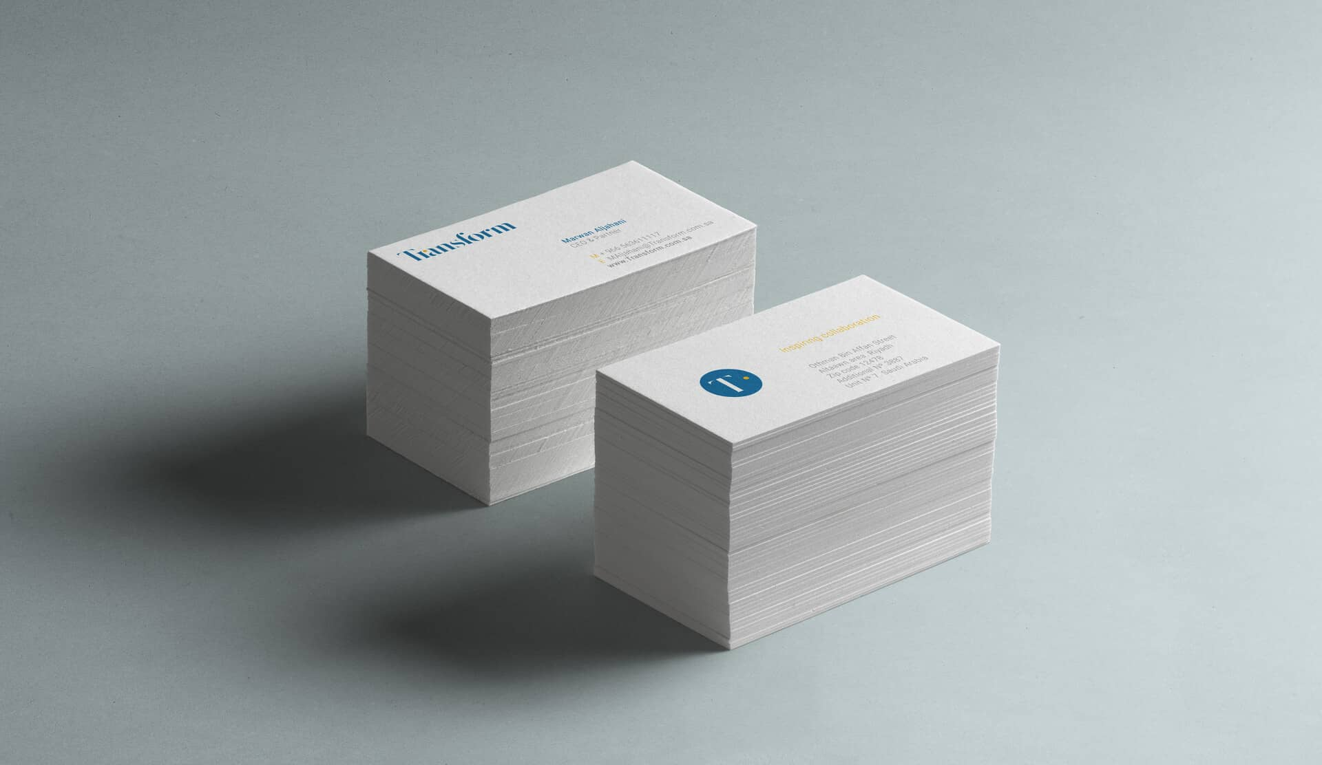 Two piles showing the two sides of Transform's business cards