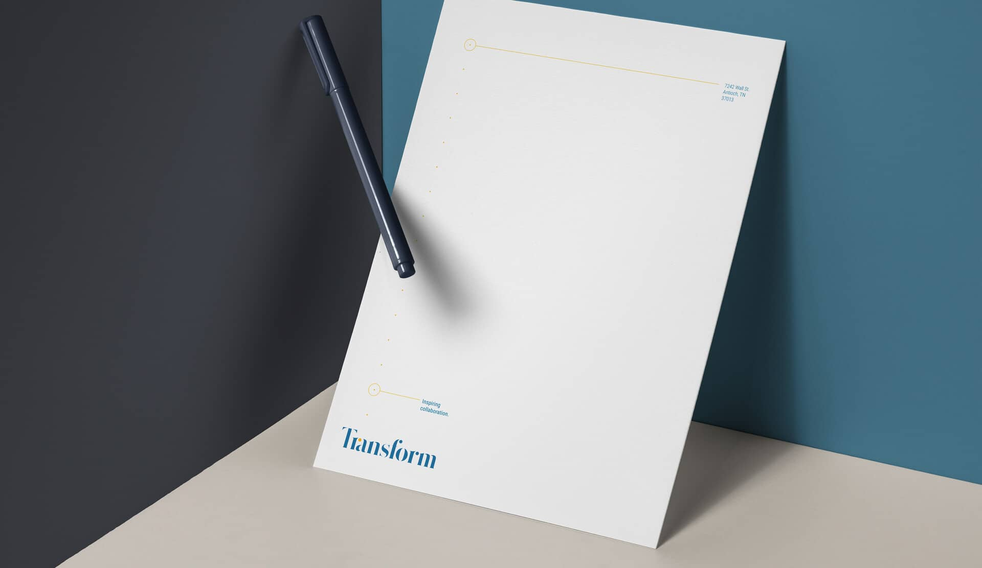 Transform letterhead design on thick paper resting on a blue background